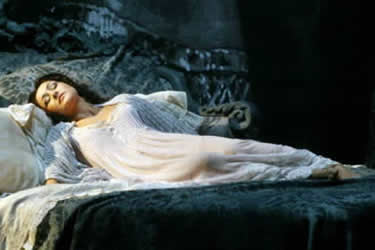 Violetta in La Traviata: a beautiful, pale woman in a white nightdress lying on a bed